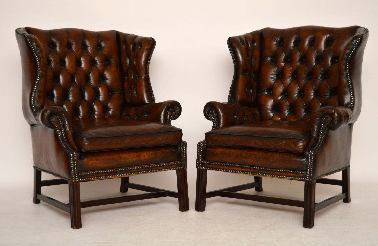 Pair of Antique Deep Buttoned Leather Wing Armchairs